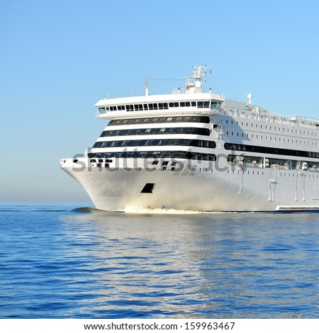White passenger ferry ship sailing in still water - stock photo