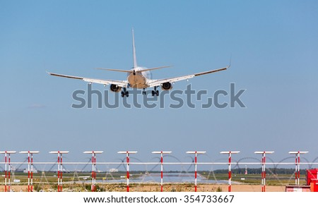white passenger jet with the gear landing at airport on blue sky background - stock photo