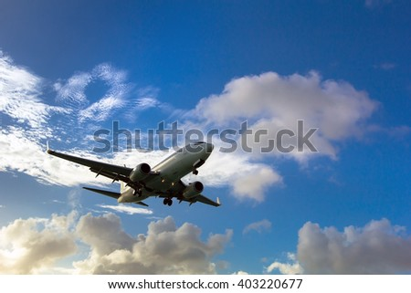 White passenger plane. Aircraft is flying in blue cloudy sky. - stock photo