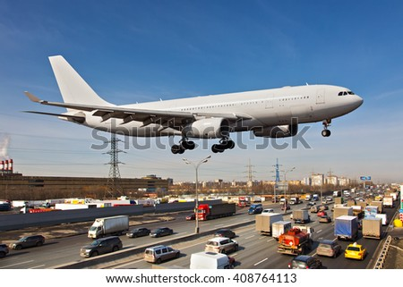 White passenger plane. Aircraft is flying very low over the highway and cars. - stock photo