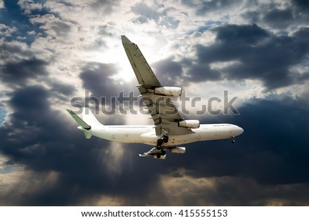 White passenger plane in the sky. Aircraft is flies against the backdrop of sun and storm clouds. - stock photo