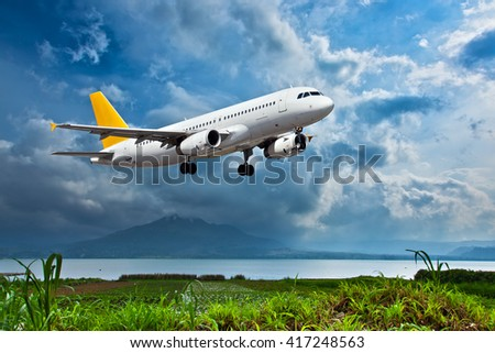White passenger plane with yellow Tail is climbing in the cloudy sky. Aircraft flies over green grass and lake with mountain at the background. - stock photo