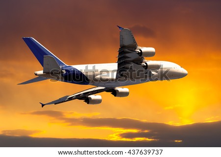 White passenger wide-body airplane. Aircraft is flying in the sunset orange sky. - stock photo
