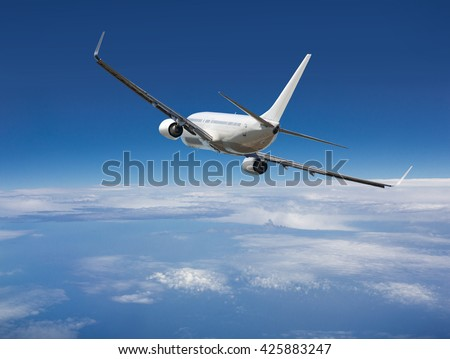 White passenger wide-body plane. Aircraft is flying in blue cloudy sky over the sea. - stock photo