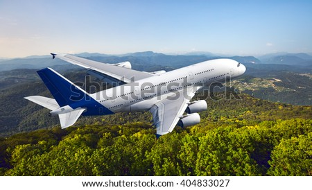 White passenger wide-body plane with blue tail. Aircraft is flying over the green wooded hills. - stock photo