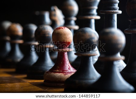 White pawn in line of black pawn chess pieces - stock photo
