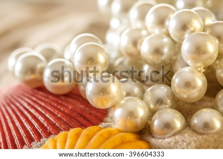 White pearl and seashells on sand background - stock photo