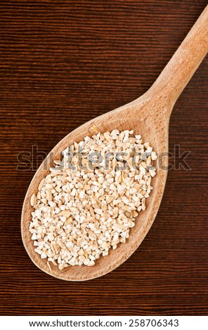 White pearled barley groats portion, coarsely grains portion on wooden spoon lying on dark board closeup, healthy raw food heap in day light, vertical orientation, nobody. - stock photo