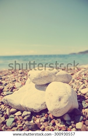 White pebbles on the beach, on a sunny summer day. Image edited in faded, washed out, retro, Instagram style with red filter and dark vignette; summer vintage concept.  - stock photo