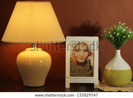 White photo frame and lamp on wooden table on brown wall background - stock photo