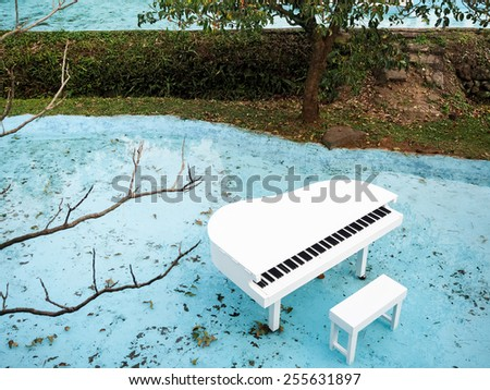 white piano at pond - stock photo