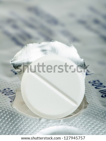 White pill in a pack very close up. Macro studio shot - stock photo