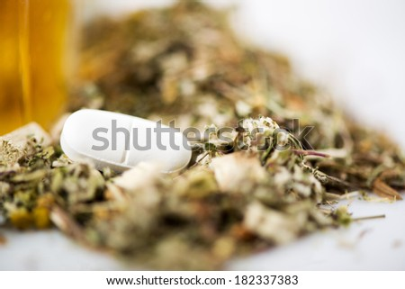 White Pill on herbal background. Selective focus. The focus is on the pill. - stock photo