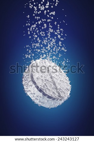 White pill surrounded by air bubbles to emulate the dissolution of a tablet in water - stock photo