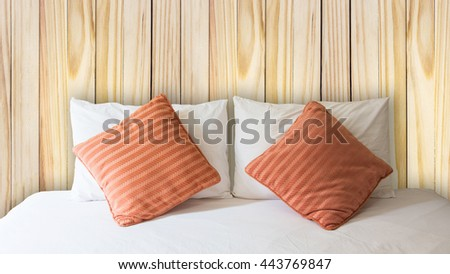 white pillow and orange pillow on bed and with blanket in vintage wooden bedroom - stock photo