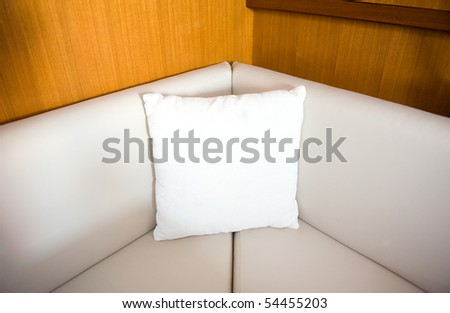 white pillow on a corner of white sofa , in a luxury yacht. - stock photo