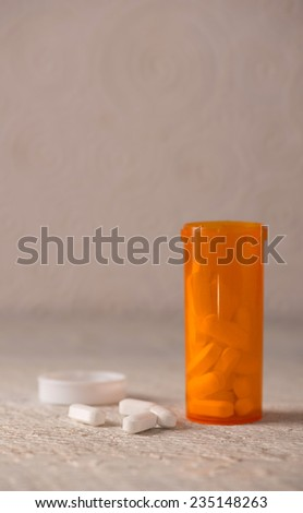 White pills and bottle on neutral background which can be use for drug abuse or medical use concepts - stock photo