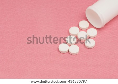 White pills and pill bottle on pink background. Room for text on left. Selective focusing. - stock photo