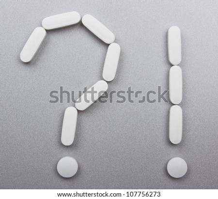 White pills laid out in the form of exclamation and query marks on gray background - stock photo