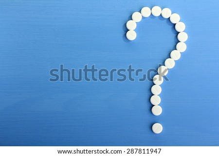 White pills on a blue background - stock photo