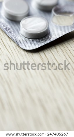 White pills strip on wooden table. Copy space. Slightly defocused and closeup shot. - stock photo