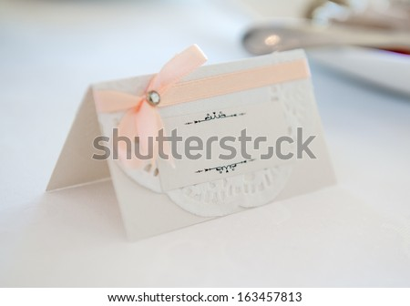 White place card decorated with orange bow - stock photo