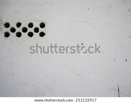 white plastered wall with holes - stock photo