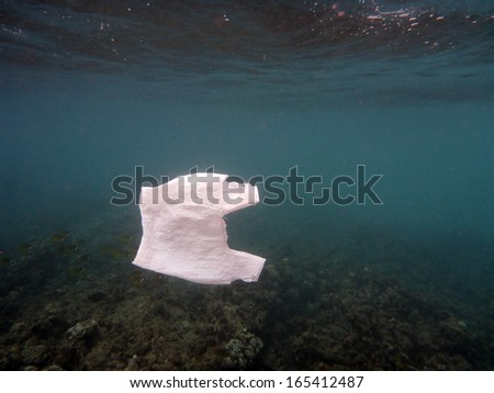White Plastic Bag floats in the water of the ocean of Hanauma Bay on Oahu, Hawaii.  With Coral and fish in the distant background and sun light shining through the surface. - stock photo