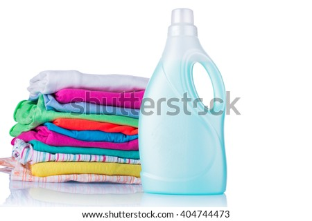 White plastic bottle of detergent and a pile of clean laundry on a white background. Conditioner for linen - stock photo