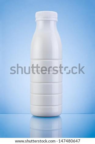 White Plastic bottle of milk on a blue background - stock photo