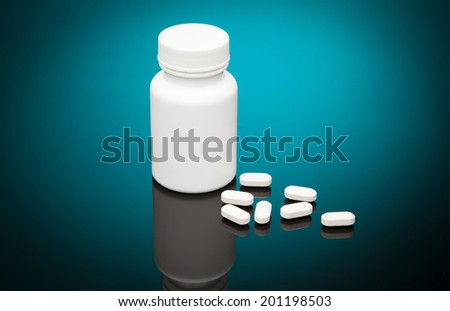 White plastic bottle with white vitamins in a mirror whit blue reflection. - stock photo