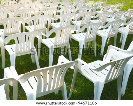 White plastic chairs arranged in rows on green grass - stock photo