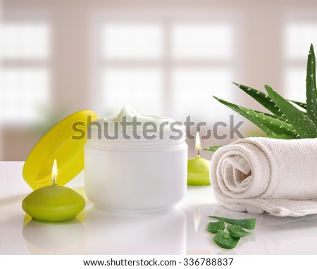 White plastic container with facial or body aloe vera cream. Candles, towel and plant decoration and windows background. Square composition. Front view - stock photo