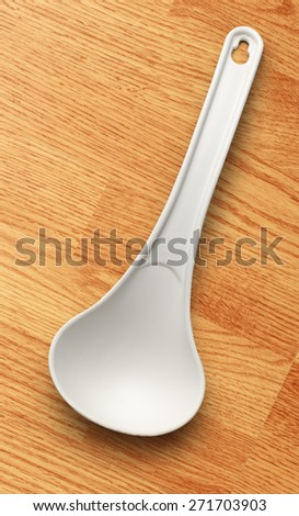 White plastic ladle on the wooden background - stock photo