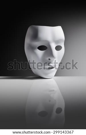 White plastic mask on reflective surface. - stock photo