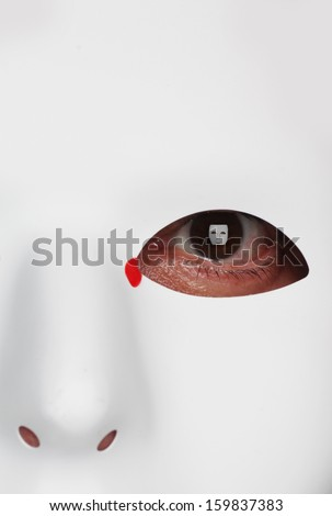 White plastic mask with focus on eye, catch light an image of the same mask full face with tiny red droplet on inner tear duct - stock photo