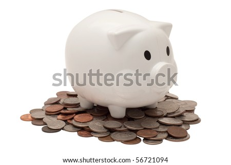 White plastic piggy bank on a pile of us currency coins. Isolated on white background, saved with clipping path - stock photo