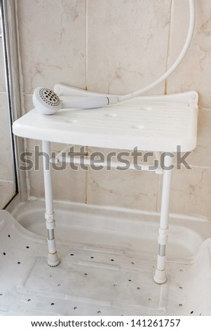 White Plastic shower seat used by the elderly and disabled to aid them by allowing them to sit and wash often reccommended by occupational therapists - stock photo
