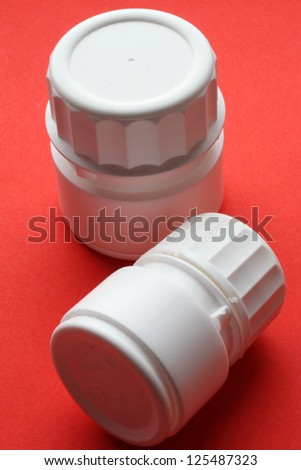 white plastic vessesl for pills collection on red background - stock photo