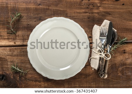 White Plate and Cutlery on Rustic Old Wooden Table  - stock photo