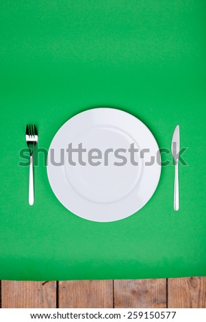 white plate, fork and knife on green background - stock photo