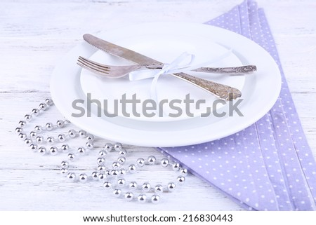 White plate, fork, knife and Christmas decoration on lilac polka dot napkin on wooden background - stock photo