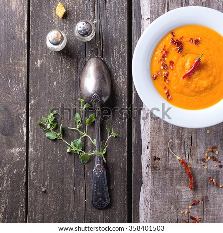 White plate of carrot cream soup with red hot chili pepper. Over old wooden table with vintage spoon, peppers, salt and croutons. Top view. Rustic style. Square image - stock photo