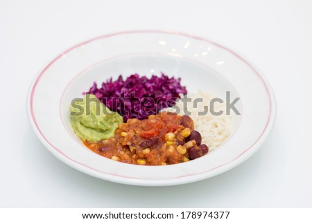 White plate of chili sin carne with red cabbage, guacamole and rice on white background - stock photo