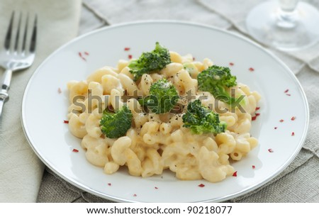 White plate of fresh homemade macaroni and cheese with broccoli and red pepper - stock photo