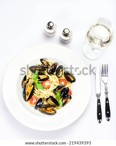 White plate of italian pasta with mussels, cherry tomato  and herbs for a tasty seafood meal closeup over white tablecloth - stock photo