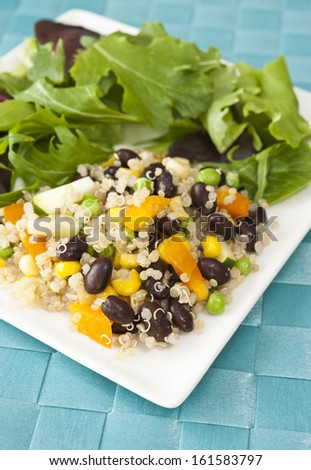 White plate of quinoa and vegetable salad on a blue mat - stock photo