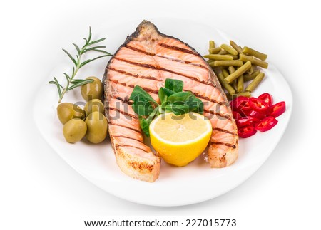 White plate of salmon steak with vegetables. Isolated on a white background. - stock photo