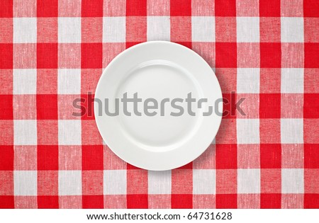 white plate on red checked tablecloth - stock photo