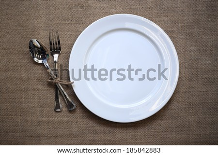 white plate, spoon and fork on old wooden table. - stock photo